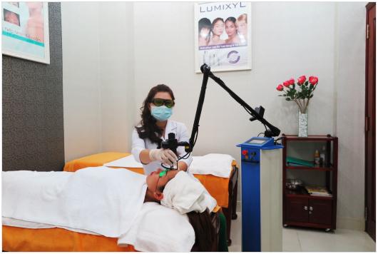 Bác sỹ đang chiếu Laser điều trị cho khách